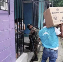 Military accompanied by GANA or Nuevas Ideas (logo on vest used to be Nuevas Ideas) party members deliver a box of goods to Salvadoran families in violation of campaign laws.
